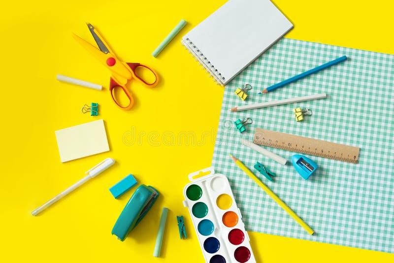 在黄色和蓝色方格的背景的学校用品 库存照片