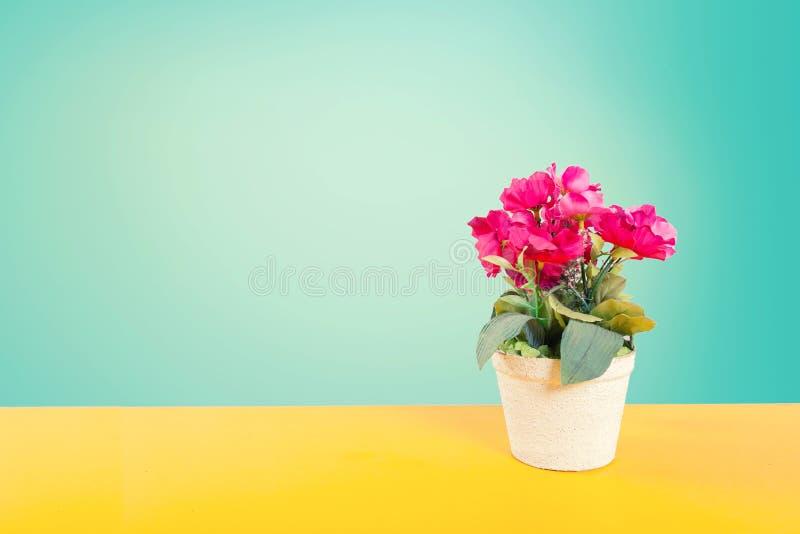在黄色地板的人造花罐与绿色光滑的背景和葡萄酒styl定调子 免版税库存照片