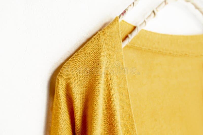 在黄色垂悬的一件羊毛衫在白色背景的晒衣架 免版税库存照片