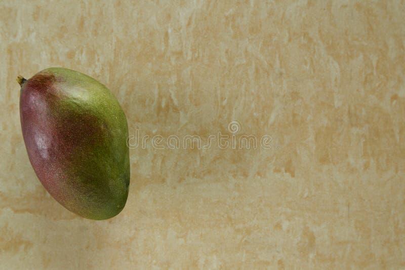 在黄色大理石背景的绿色芒果 图库摄影