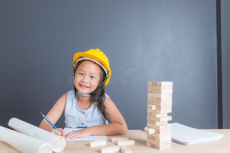 在黄色安全帽的年轻亚洲泰国女孩孩子 库存图片