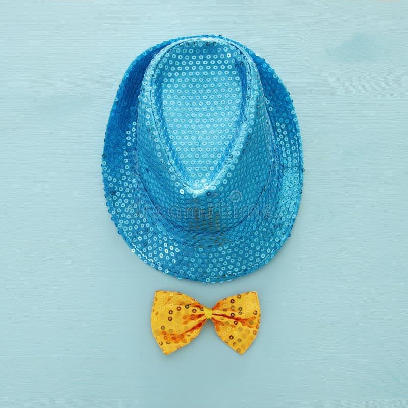 在黄色弓旁边的蓝色发光的闪光金属片的党帽子在木背景 普珥节庆祝概念 库存照片