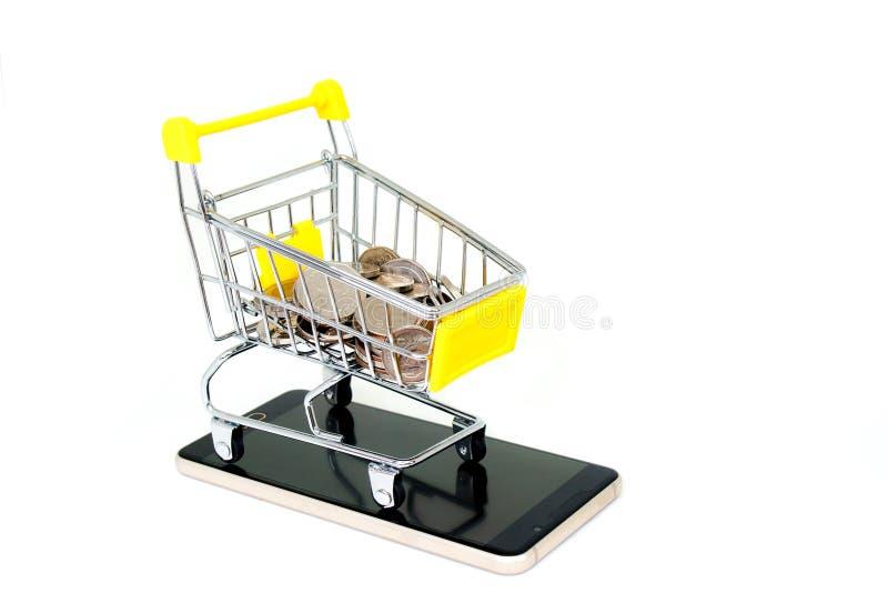 在黄色微型购物车或超级市场台车设置的各种各样的银色金钱硬币在白色背景隔绝的智能手机 免版税库存照片