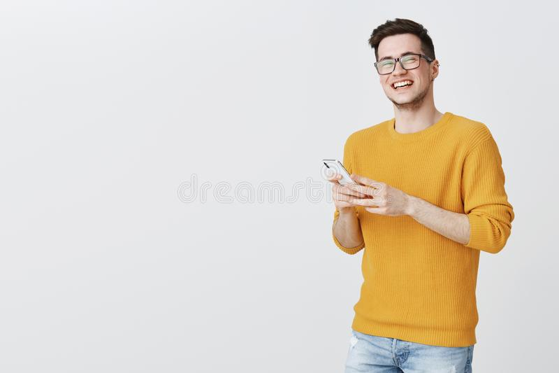 在黄色温暖的毛线衣的笑大声注视的无忧无虑的愉快和满意的英俊的年轻白种人男性画象  库存图片