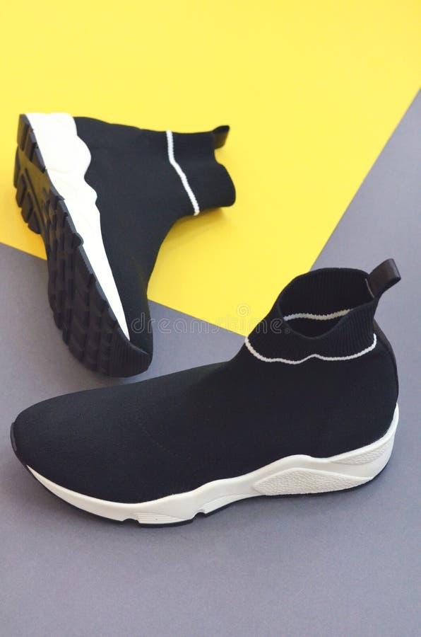 在黄色灰色背景的时兴的黑运动鞋 库存照片