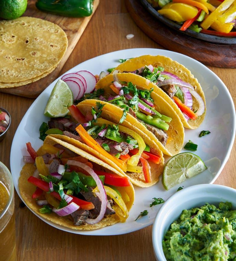 在黄色玉米粉薄烙饼的墨西哥法加它炸玉米饼供食与鳄梨调味酱捣碎的鳄梨酱 库存图片