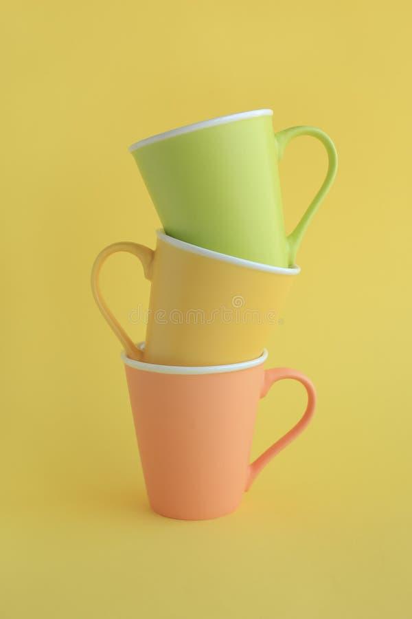 在黄色的三个五颜六色的杯子 库存图片