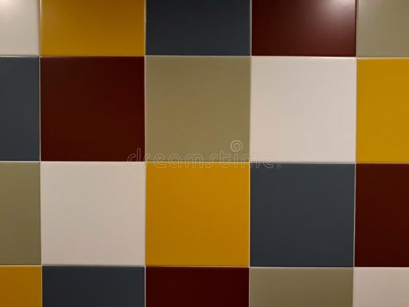 在黄色的方形的瓦片,绿色,红色,灰色在背景的墙壁上 免版税库存照片