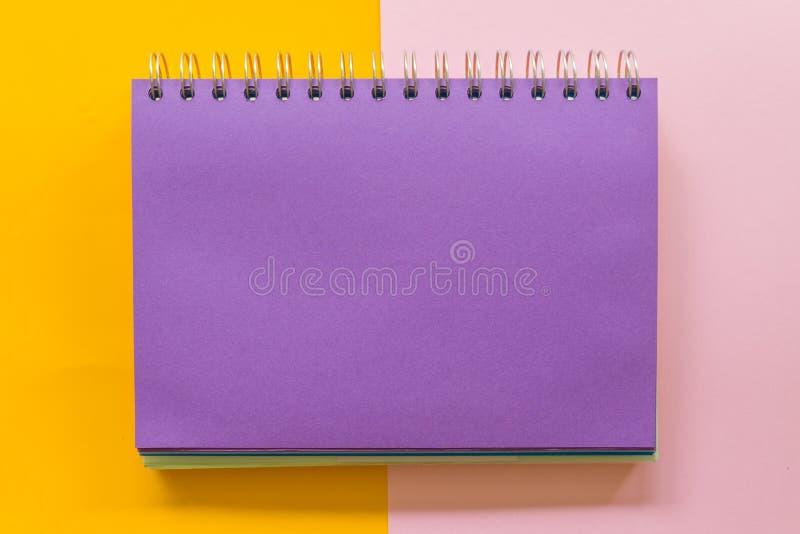 在黄色粉红彩笔背景的紫色笔记本 免版税库存图片