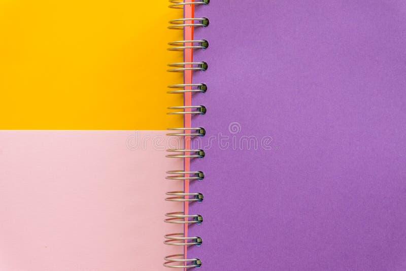 在黄色粉红彩笔背景的紫色笔记本 库存照片