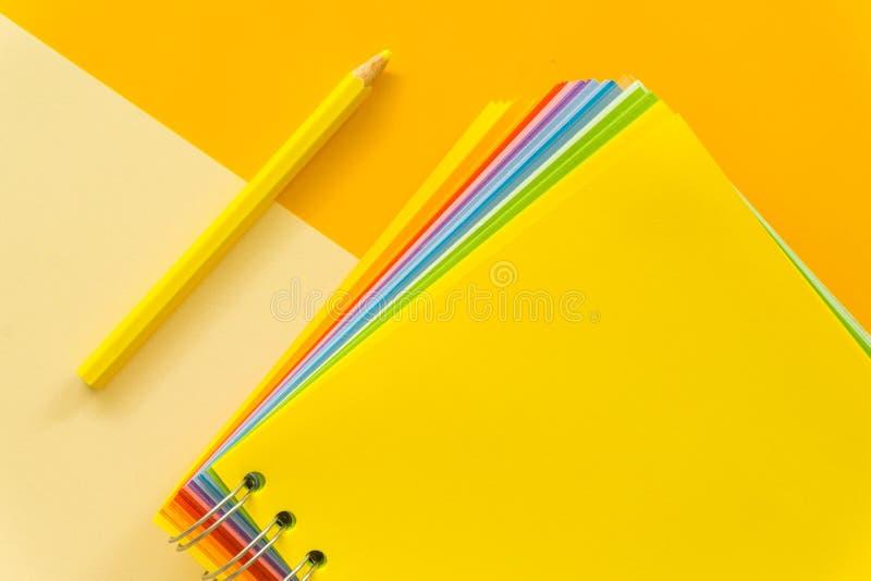 在黄色粉红彩笔背景的黄色笔记本 免版税库存图片