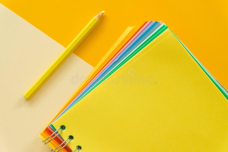 在黄色粉红彩笔背景的黄色笔记本 库存图片