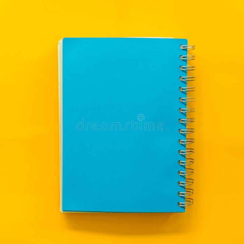 在黄色粉红彩笔背景的Bule笔记本 库存图片