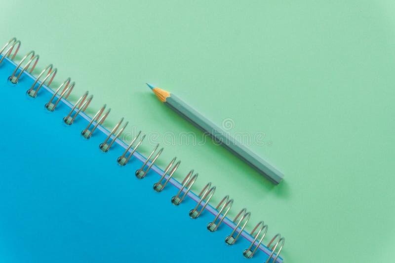 在黄色粉红彩笔背景的Bule笔记本 免版税库存图片