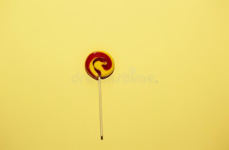 在黄色纸背景的红色,黄色颜色棒棒糖 库存图片