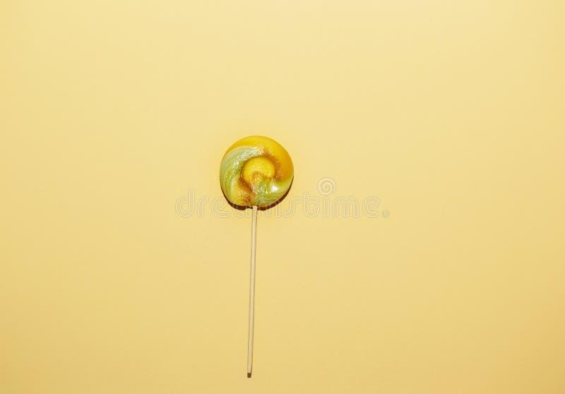 在黄色纸背景的红色,黄色颜色棒棒糖 库存照片
