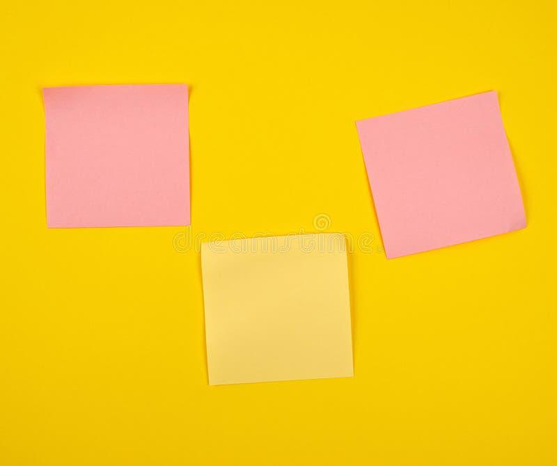在黄色背景和黄色纸贴纸黏贴的桃红色 图库摄影