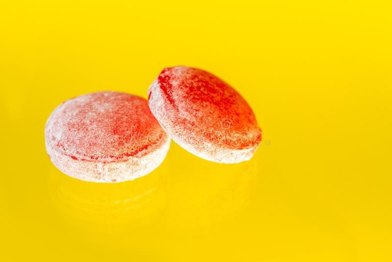 在黄色背景洒的甜棒棒糖 免版税库存照片