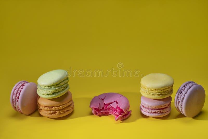 在黄色背景特写镜头的多彩多姿的通心面曲奇饼 被咬住的一 E 免版税库存图片