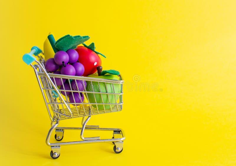 在黄色背景用果子,拷贝空间的微型购物的台车 免版税库存图片