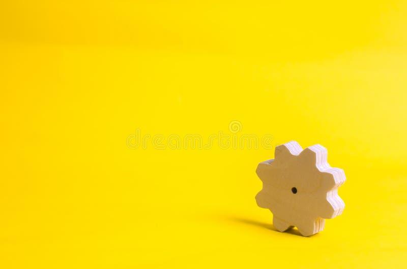 在黄色背景的一个木齿轮 技术和商业运作的概念 简单派 机制和设备 工作, 免版税库存照片