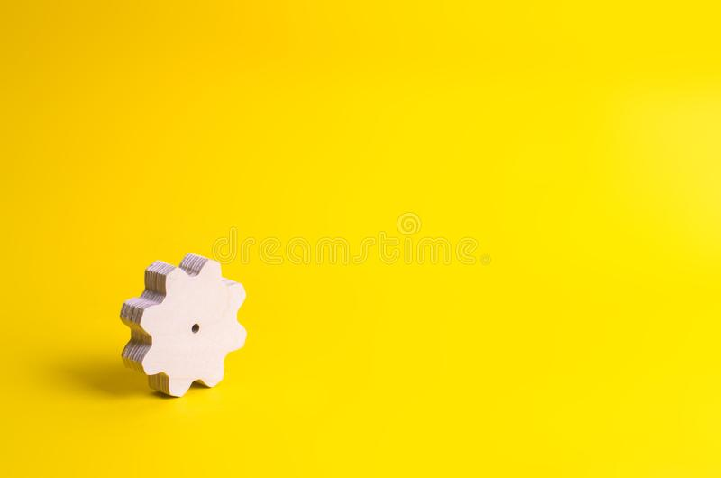在黄色背景的一个木齿轮 技术的概念 库存照片