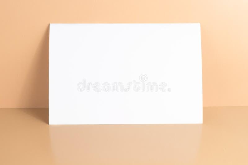 在黄色背景的一个空白的白色明信片/飞行物/邀请大模型 免版税库存图片