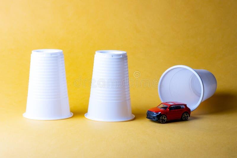 在黄色背景的三个塑料一次性杯子,在他们中的一个以下掩藏一辆汽车 免版税图库摄影