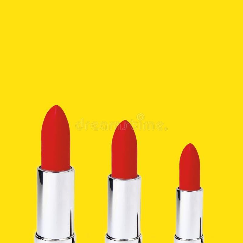 在黄色背景的三红色唇膏 免版税库存图片