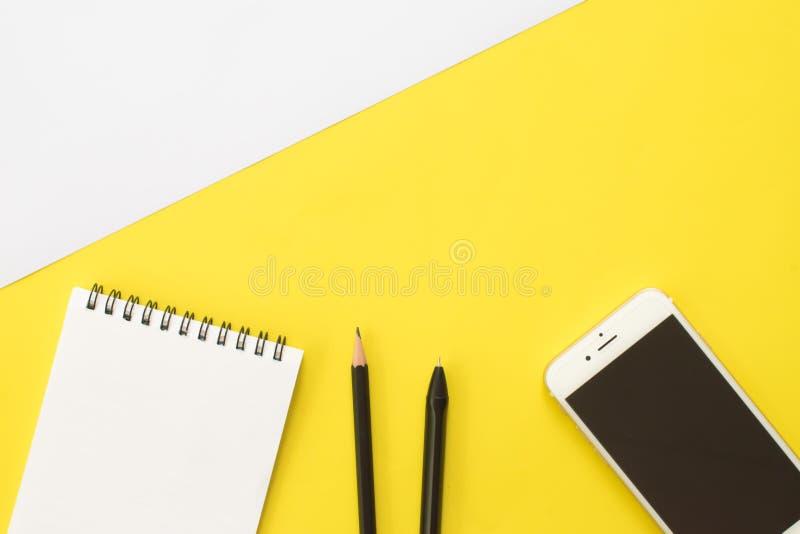在黄色背景的书、铅笔、笔、智能手机和眼睛玻璃 生活方式工作区,顶视图 库存图片