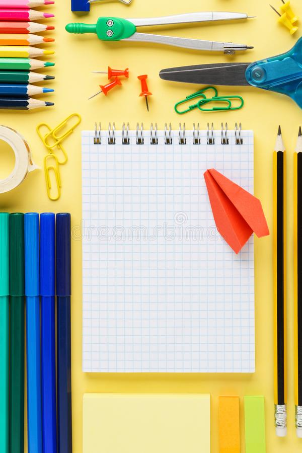 在黄色背景的五颜六色的学校文具收藏 免版税库存图片