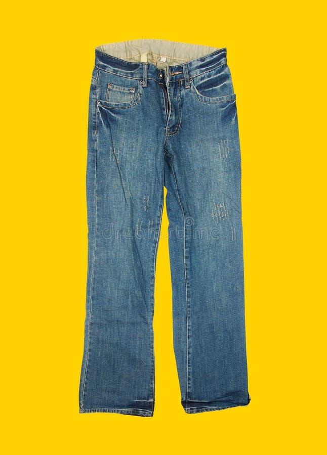 在黄色背景的偶然牛仔裤 免版税库存图片