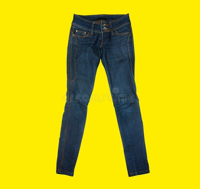 在黄色背景的偶然牛仔裤 免版税库存照片