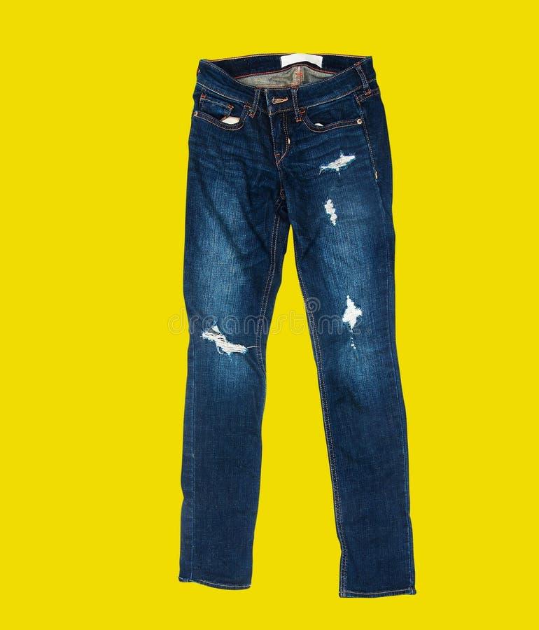在黄色背景的偶然牛仔裤 库存照片