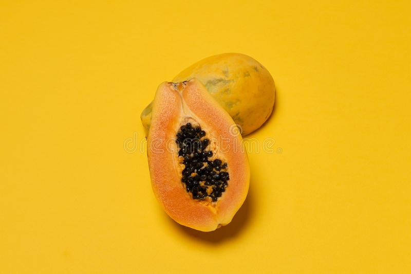 在黄色背景的半新鲜的成熟番木瓜 库存照片