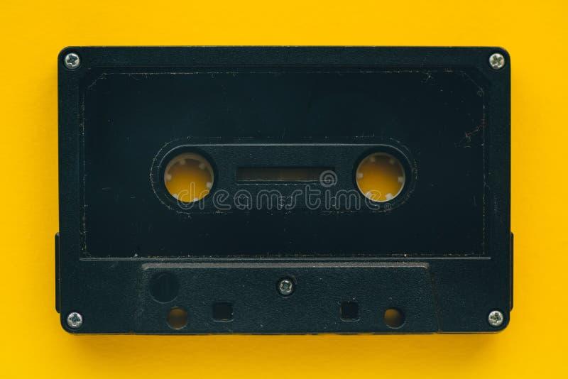 在黄色背景的卡型盒式录音机磁带 库存图片