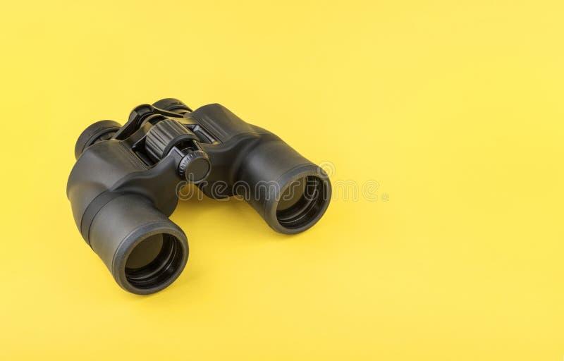 在黄色背景的双筒望远镜 免版税库存图片