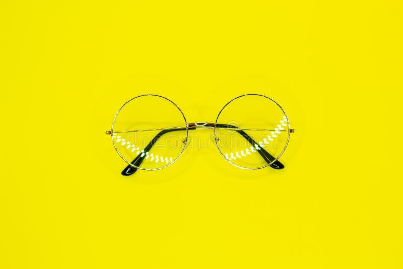 在黄色背景的圆的玻璃 一个清晰视界的时装配件 库存图片