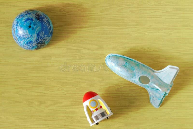在黄色背景的太空火箭玩具行星塑料塑造的飞机 库存图片