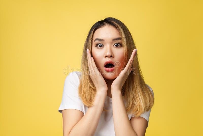 在黄色背景的惊奇的年轻亚洲妇女面孔孤立 库存图片