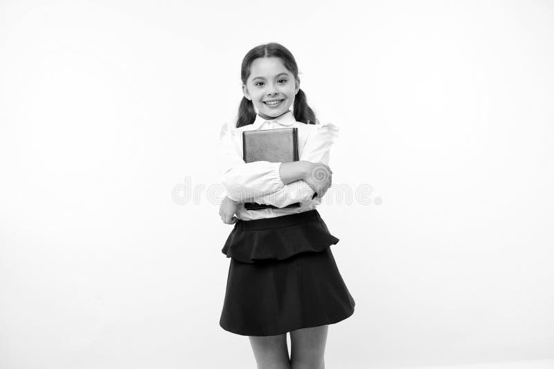 在黄色背景的愉快的女孩举行书 与课本的小的女小学生微笑 时尚书痴 日第一所学校 图库摄影