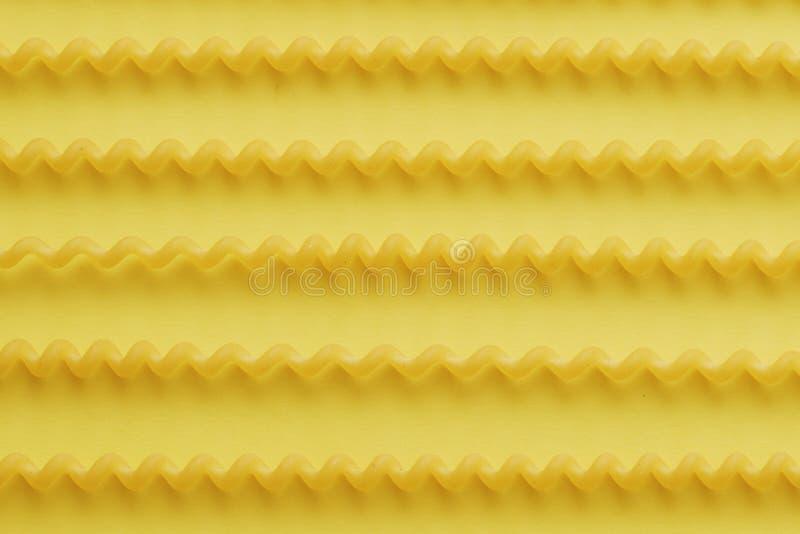 在黄色背景的未加工的fusilli lunghi面团 库存照片