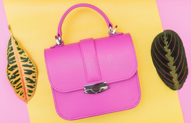 在黄色背景的桃红色时尚袋子 库存图片