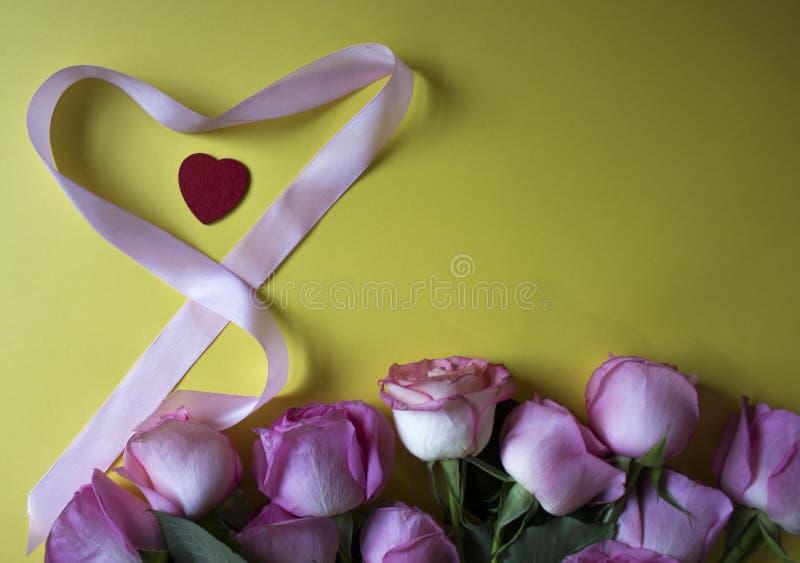 在黄色背景的桃红色玫瑰、红心和心形丝带 库存图片