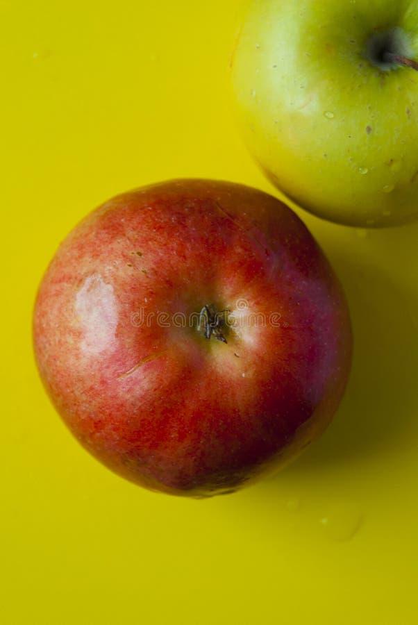 在黄色背景的水多的红色和绿色苹果计算机 库存图片