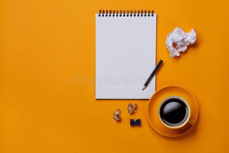 在黄色背景的白色笔记薄与铅笔和纸 库存照片
