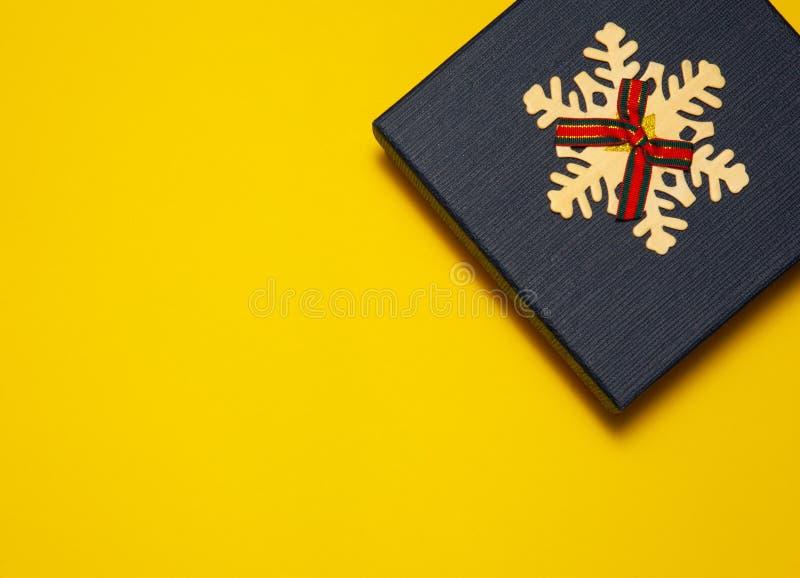 在黄色背景的礼物盒蓝色,文本的地方 圣诞节假日或生日的概念 免版税库存图片