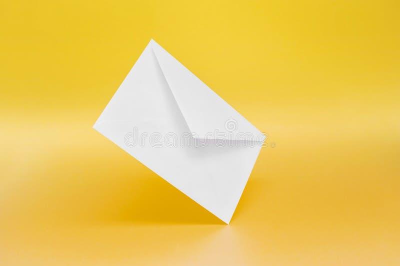 在黄色背景的空的纸信封 库存图片
