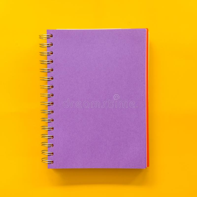 在黄色背景的紫色笔记本 免版税库存照片
