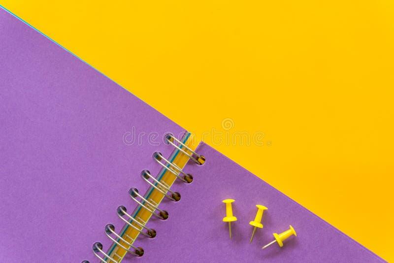 在黄色背景的紫色笔记本 免版税库存图片
